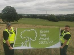 Two people holding a green flag in front of a rolling park view
