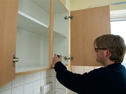 A man fixing a cupboard