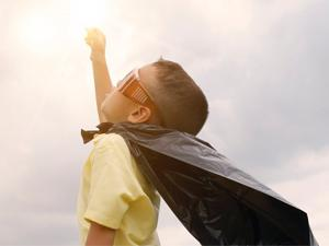 Young boy dressed as super hero pointing to the sky