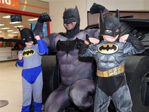 Two young boys dressed up as superheroes next to Batman
